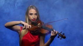 Het meisjesblonde speelt de viool Rokerige achtergrond Langzame Motie stock videobeelden