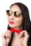 Het meisjesbrunette in zonnebril maakt zijn vlinderdasrood recht Stock Foto