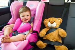 Het meisjesglimlach van de baby in auto Stock Afbeelding