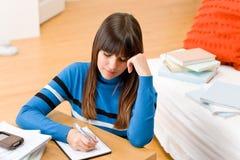 Het meisjeshuis van de tiener - de student schrijft thuiswerk Stock Afbeeldingen
