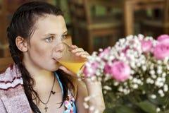 Het meisjeskind drinkt sap in koffie stock fotografie