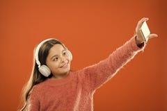 Het meisjeskind luistert muziek moderne hoofdtelefoons en smartphone nemend selfie Krijg muziekabonnement Geniet muziek van conce royalty-vrije stock foto