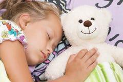 Het meisjeskind slaapt met teddybeer Stock Foto