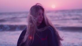 Het meisjesmodel kijkt in de camera, kant Dawn, overzees, golven, horizon, wind op de achtergrond stock videobeelden
