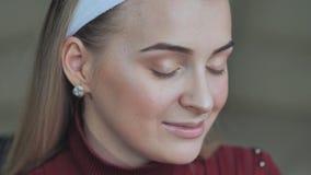 Het meisjesmodel toont haar ooglidmake-up aan stock footage