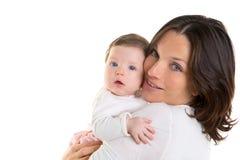 Het meisjesomhelzing van de baby in moederwapens op wit Royalty-vrije Stock Foto's