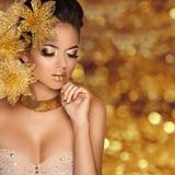 Het Meisjesportret van de manierschoonheid met bloemen die op gouden wordt geïsoleerd Royalty-vrije Stock Foto's