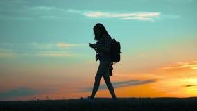 Het meisjesreiziger van de silhouetwandelaar met het onderzoeksmanieren van de smartphonenavigatie de langzame navigatie van de h stock footage