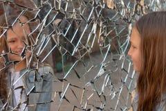 Het meisjesschoolmeisje kijkt droevig in de gebroken spiegel stock fotografie