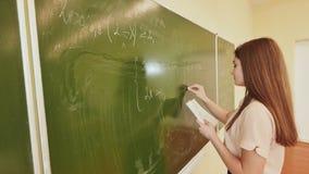 Het meisjesschoolmeisje schrijft op de bord wiskundige formules stock video