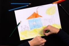 Het meisjesschoolmeisje trekt een kleurpotlood stock fotografie