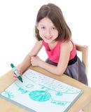 Het meisjesschoolmeisje zit bij een lijst Royalty-vrije Stock Afbeeldingen