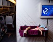 Het meisjesslaap van de baby in een mandewieg op een vliegtuig Stock Afbeelding