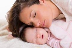 Het meisjesslaap van de baby met moederzorg dichtbij Royalty-vrije Stock Foto's
