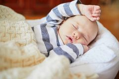 het meisjesslaap van de 1 maand oude baby onder gebreide deken Stock Foto's