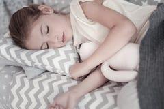 Het meisjesslaap van Nice met haar stuk speelgoed stock afbeelding