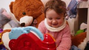 Het meisjesspelen en dansen van de peuterbaby in haar ruimte met speelgoed stock video