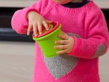 Het meisjesspelen van de peuterbaby met gekleurde koppen Stock Fotografie