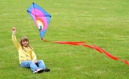 Het meisjesspelen van het kind met vlieger Royalty-vrije Stock Afbeeldingen