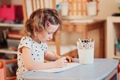 Het meisjestekening van het kleuterkind met potloden thuis Stock Afbeeldingen