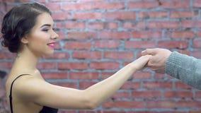 Het meisjesverblijf in bustehouder, mensenaanbieding een hand voor dans, dan werpt het verrassing schok stock footage