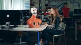 Het meisjeswerk met androïde, sluit omhoog Robotachtige androïde bij ingenieurslaboratorium stock footage