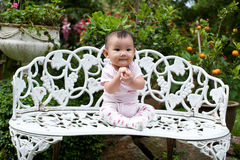 het meisjeszitting van de 7 maand oude Aziatische baby op witte stoel Stock Fotografie