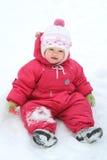 Het meisjeszitting van de baby in de sneeuw Stock Afbeeldingen