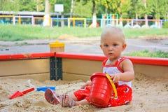 Het meisjeszitting van de baby het spelen in een zandbak Stock Foto