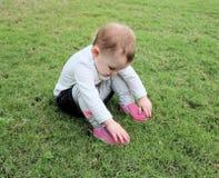 Het meisjeszitting van de baby op gras Stock Afbeelding