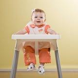 Het meisjeszitting van de baby in te voeden highchairwachten Stock Afbeelding