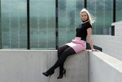 Het meisjeszitting van de blonde Stock Foto's