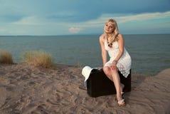 Het meisjeszitting van de blonde op een koffer bij het strand Stock Foto