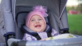 Het meisjezitting van Ð ¡ Ute in kinderwagen en smilingб op de straat, aard stock footage