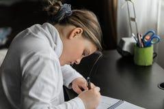 Het meisjezitting van Nice achter de lijst en het doen van het huiswerk in haar ruimte in ochtendtijd Royalty-vrije Stock Foto's