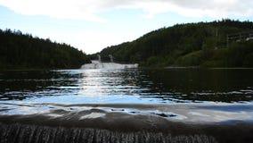 Het melkachtige witte bergstroom van de riviervloed over concrete barrière in de zomerzonneschijn met hydroelektrische centrale o stock video