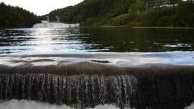 Het melkachtige witte bergstroom van de riviervloed over concrete barrière in de zomerzonneschijn met hydroelektrische centrale o stock videobeelden