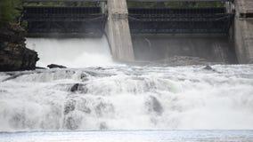 Het melkachtige witte bergstroom van de riviervloed over concrete barrière in de zomerzonneschijn met hydroelektrische centrale o stock footage