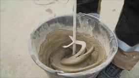 Het mengen van concreet pleister met elektrische mixer Beweeg de oplossing in een emmer stock videobeelden