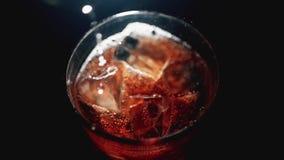 Het mengen van een kola met ijsblokjes in een glas Sluit omhoog Langzame motie 100fps stock video
