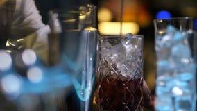 Het mengen van glas met ijs en alcohol die zich op bar bevinden stock videobeelden