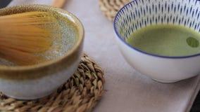 het mengen van groene theematcha in een kom op blauwe oppervlakte stock videobeelden