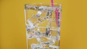 Het mengen van koud waterdrank met roze het drinken stro Glashoogtepunt van bruisende ijsblokjes stock video