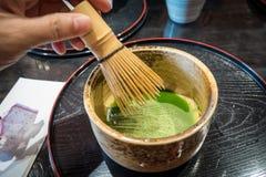 Het mengen van matcha groene thee in ceramische kop Japanse groene thee stock afbeelding
