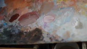 Het mengen van verf op palet, close-up een schilder met een lange die borstel van natuurlijke doekmengsels wordt gemaakt schilder stock footage