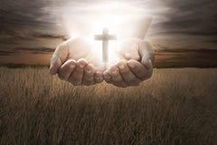 Het menselijke christelijke kruis van de handgreep Royalty-vrije Stock Foto's