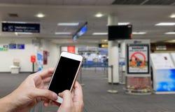 Het menselijke holdings lege scherm van slim telefoon en wachtenvertrek Royalty-vrije Stock Afbeelding