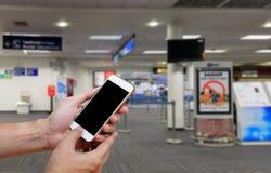 Het menselijke holdings lege scherm van slim telefoon en wachtenvertrek Royalty-vrije Stock Fotografie
