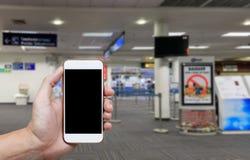 Het menselijke holdings lege scherm van slim telefoon en wachtenvertrek Stock Foto's