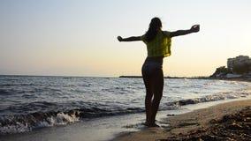 Het menselijke, Mooie jonge meisje draait geestelijk op een strandzand bij zonsondergang stock footage